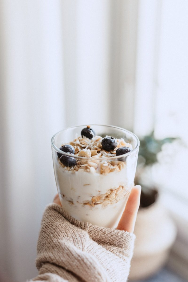Healthy meals, hand holding yogurt and granola
